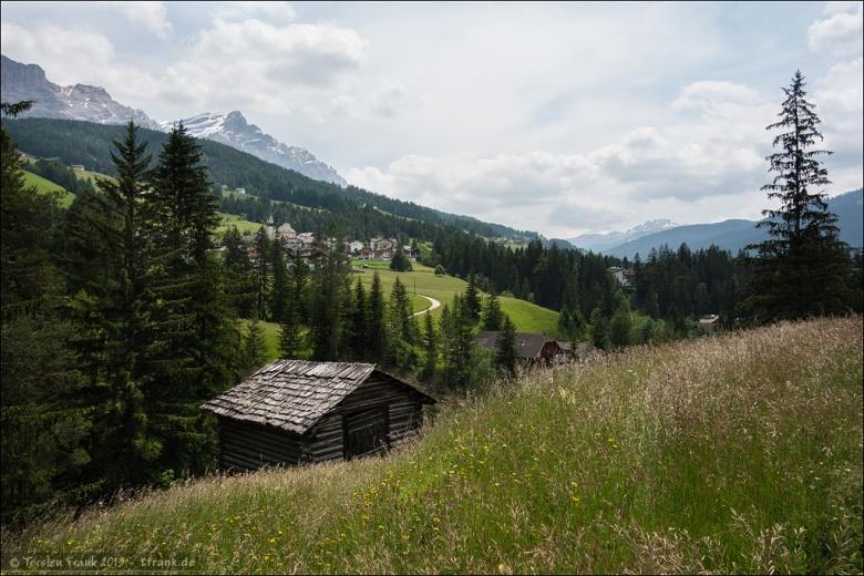 Eine Heuhütte nahe der Straße durch das Alta Badia kurz vor der Ortschaft Badia / Abtei. Im Hintergrund liegt Sankt Leonhard unterhalb des Kreuzkofels