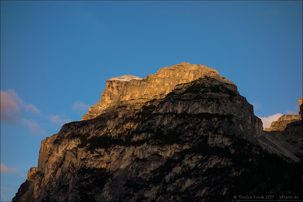 Erste Strahlen der Morgensonne kitzeln die Spitze des Sassongher
