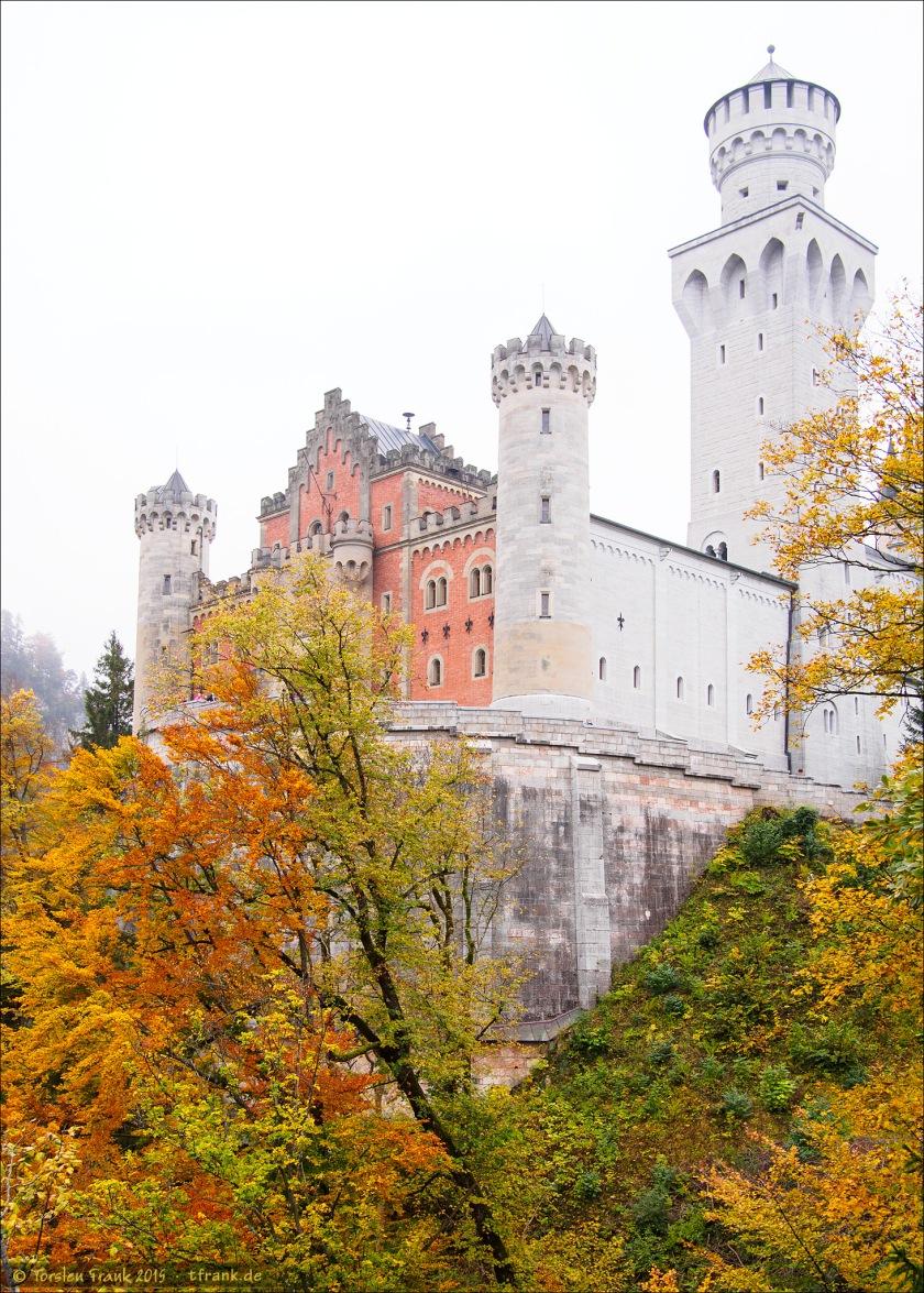 Schloss Neuschwanstein nahezu so weiß wie der Himmel - im Gegensatz zum bunten Herbstlaub.
