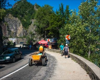 Kurz vor der Staumauer. Touris, Autofahrer und Pferdefuhrwerke teilen sich die Straße