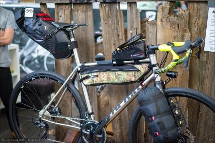 Kocmo Titan Bikes. Kocmo RR Disc mit ISP und exemplarischen Bikepacking Setup. Die Revelate Terrapin Seatpack erscheint mir (auch vom Befingern) sehr interessant mit ihrem Dryback / Harnisch-System. Die Framebag ist recht ok, denke ich. Die Oberrohrtasche würde ich persönlich niemals benutzen noch so bemessen. Viel zu breit - störender Kniekontakt garantiert. Und den Schlafsack oder ähnliches an den Gabeln zu befestigen, wäre eher ein Expeditions-Setup.
